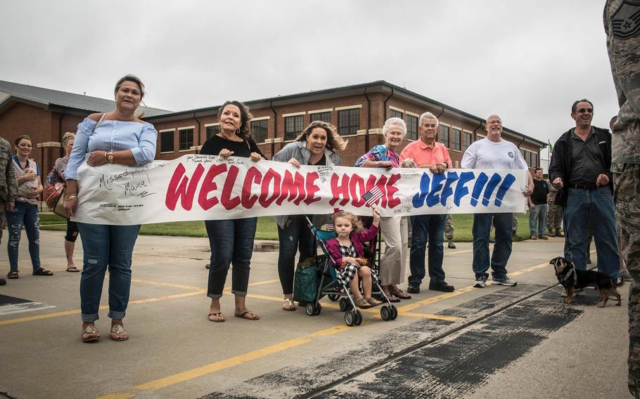 Family members of Virginia Air National Guard Staff Sgt. Jeff Greenquist, hold a welcome-home sign, celebrating his return from the Middle East at Joint Base Langley- Eustis, Va., on Thursday, Oct. 12, 2017.