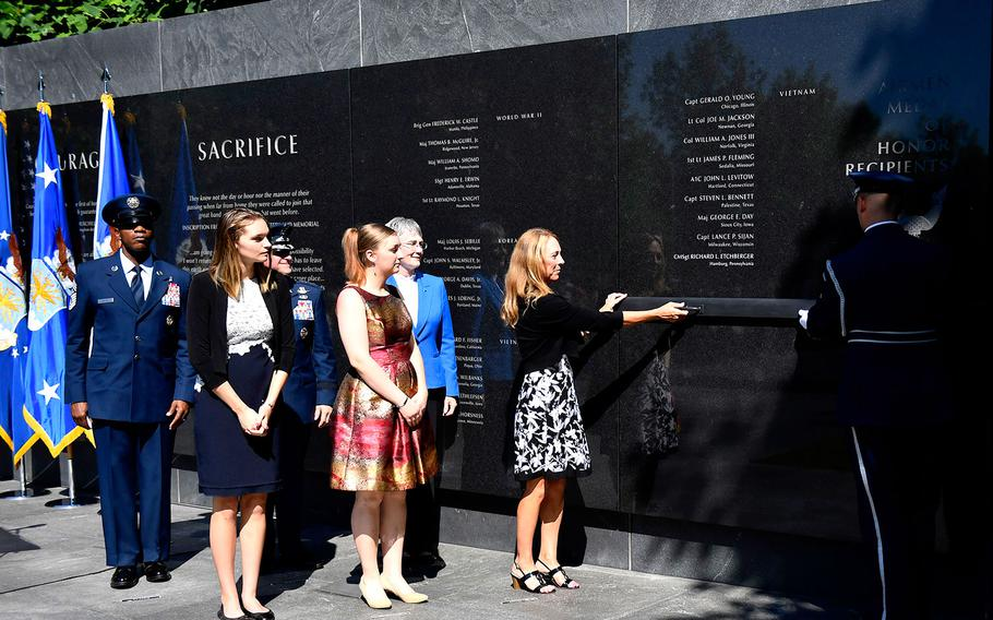 Valerie Nessel, spouse of U.S. Air Force Tech. Sgt. John Chapman, Brianna and Madison Chapman, daughters of Chapman, Secretary of the Air Force Heather Wilson, Air Force Chief of Staff Gen. David L. Goldfein and Chief Master Sgt. of the Air Force Kaleth O. Wright unveil the combat controller's name on the Air Force Memorial during a ceremony in Arlington, Va. on Aug. 24, 2018.