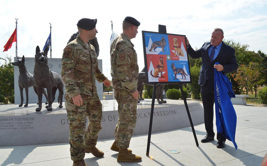 Robert Carr, San Antonio postmaster, unveils the military working dog forever stamp with Maj. Matt Kowalski and Master Sgt. Steve Kaun, both of the 341st Training Squadron, during a ceremony Thursday at military working dog memorial at Joint Base San Antonio. The new stamps are sold in sheets of 20 and honor the service of dogs in the military.