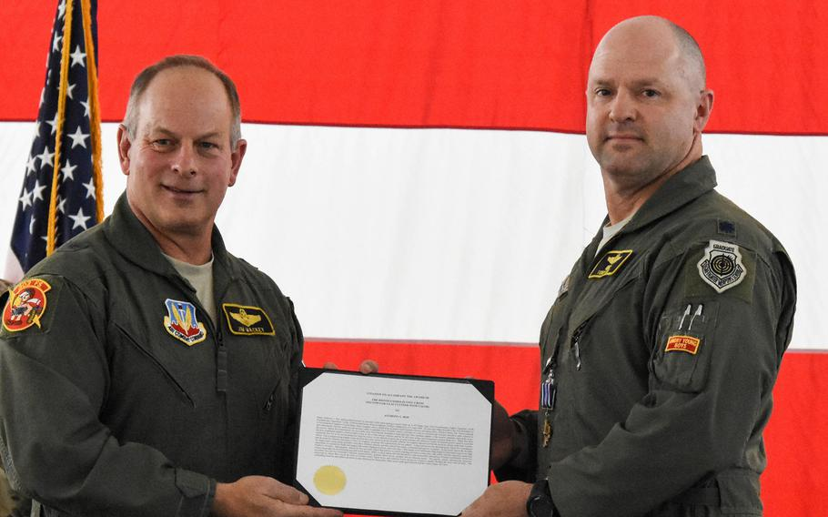 Retired Brig. Gen. Jim Mackey presents the Distinguished Flying Cross with Valor citation to Lt. Col. Anthony Roe, a flight commander with the 303rd Fighter Squadron, during a ceremony at Whiteman Air Force Base, Mo., in November of 2019. Mackey and Roe deployed to Afghanistan in 2008 and flew the mission together that earned Roe his third Distinguished Flying Cross.