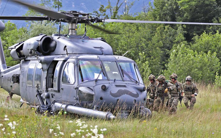 Pararescuemen with the 57th Rescue Squadron, Aviano Air Base, Italy, load a rescued downed pilot into their HH-60 Pave Hawk helicopter as part of a drill during Operation Porcupine, held at an Italian army training area located in the town of Osoppo, June 30, 2020.