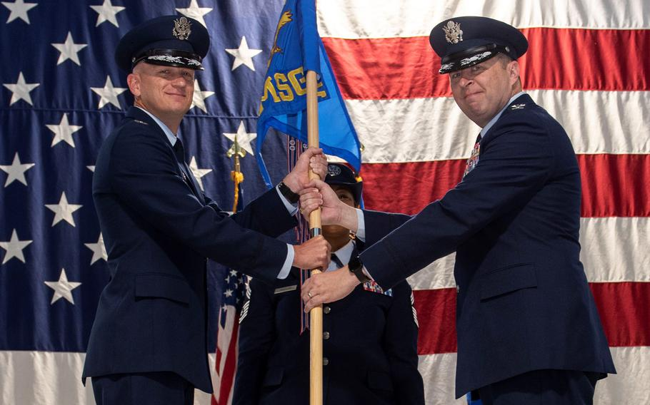 Col. Paul Miller, right, accepts the 71st Mission Support Group guidon from Col. Jay Johnson, the 71st Flying Training Wing commander in a change-of-command ceremony in Hangar 129, Vance Air Force Base, Okla.