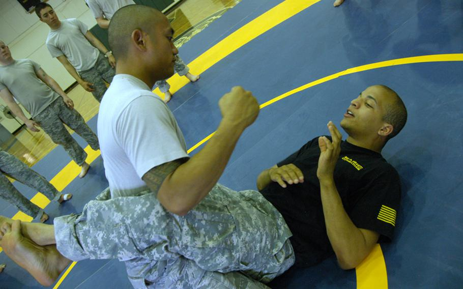 Air Force Tech Sgt. Jordan Acosta, 29, of Wahiawa, Hawaii (top) tussles with Combatives instructor Army Sgt. Matthew Prout, 26, of Baltimore at Yokota Air Base on June 24.
