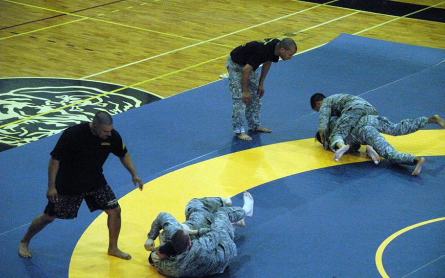 From left to right (in black T-shirts): Army Combatives instructors Leonardo Munoz, 42, and Army Sgt. Matthew Prout, 26, train airmen in hand-to-hand combat at Yokota Air Base on June 24.