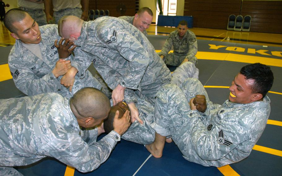 Several airmen attempt to submit Air Force Staff Sgt. Sorrell Thompson, 29, of Atlanta, Ga., during Army Combatives training at Yokota Air Base on June 24.