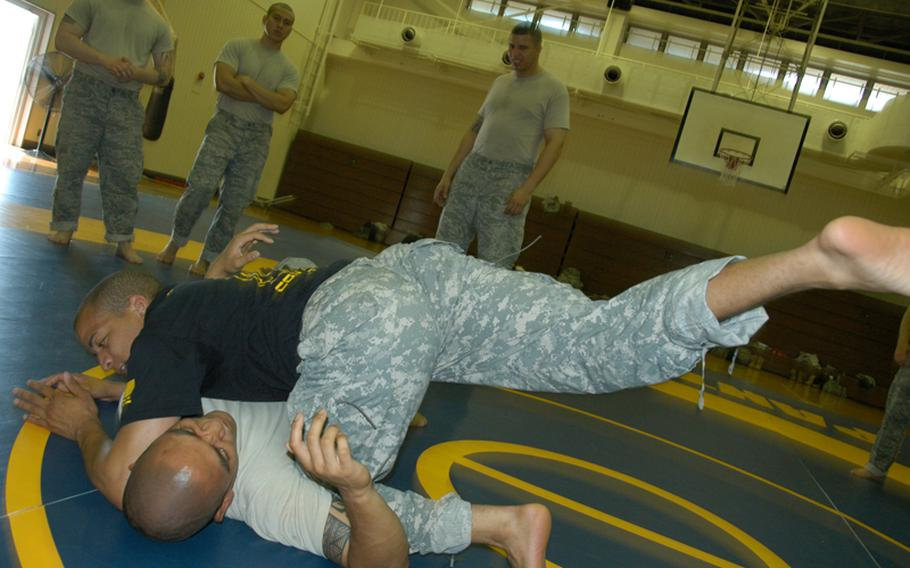 Combatives instructor Army Sgt. Matthew Prout, 26, of Baltimore, Ma. (blue shirt) demonstrates the correct way to knee an opponent in the ribs with the help of Air Force Tech Sgt. Jordan Acosta, 29, of Wahiawa, Hawaii at Yokota Air Base last Friday.