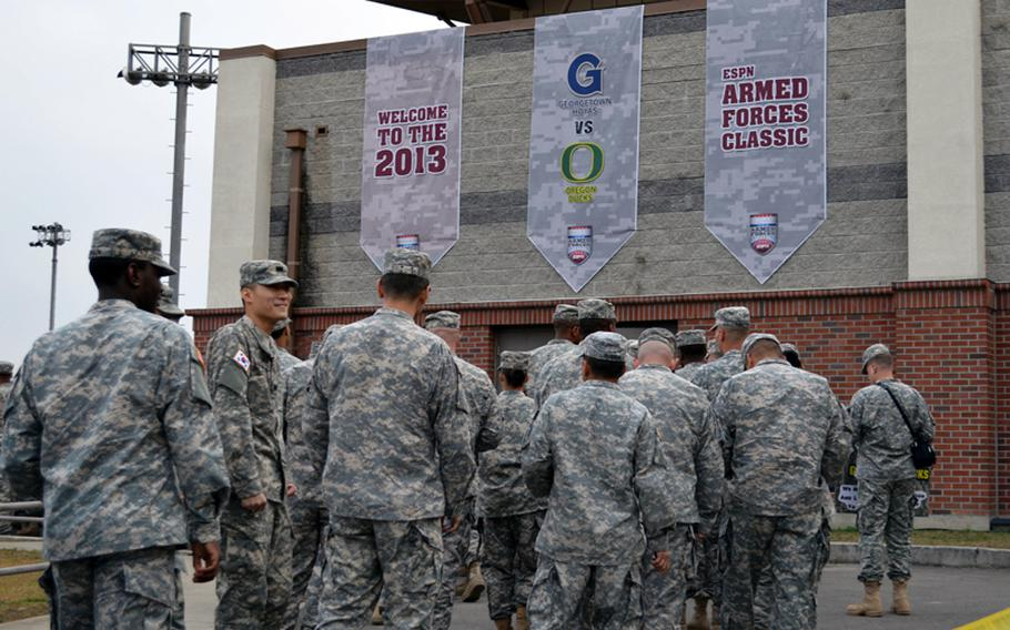 U.S. servicemembers wait to enter the Camp Humphreys Community Fitness Center in South Korea to watch the NCAA season-opening 2013 Armed Forces Classic on Saturday, Nov. 9, 2013. Oregon beat Georgetown 82-75. The televised game was part of ESPN's Veterans Week, meant to honor the U.S. military.
