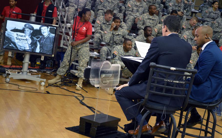 ESPN announcers prepare for the 2013 Armed Forces Classic, the NCAA's season-opener at Camp Humphreys Community Fitness Center on Saturday, Nov. 9, 2013. The monitor shows a servicemember holding up a copy of the Stars and Stripes newspaper announcing a truce in the Korean War. Oregon went on to beat Georgetown 82-75. The televised game was part of ESPN's Veterans Week, meant to honor the U.S. military.