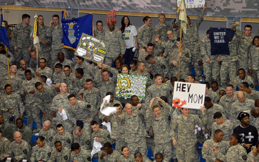 U.S. servicemembers cheer and wave signs during the 2013 Armed Forces Classic basketball game, held at the Camp Humphreys Community Fitness Center in South Korea on Saturday, Nov. 9, 2013. Oregon went on to beat Georgetown 82-75. The televised game was part of ESPN's Veterans Week, meant to honor the U.S. military.