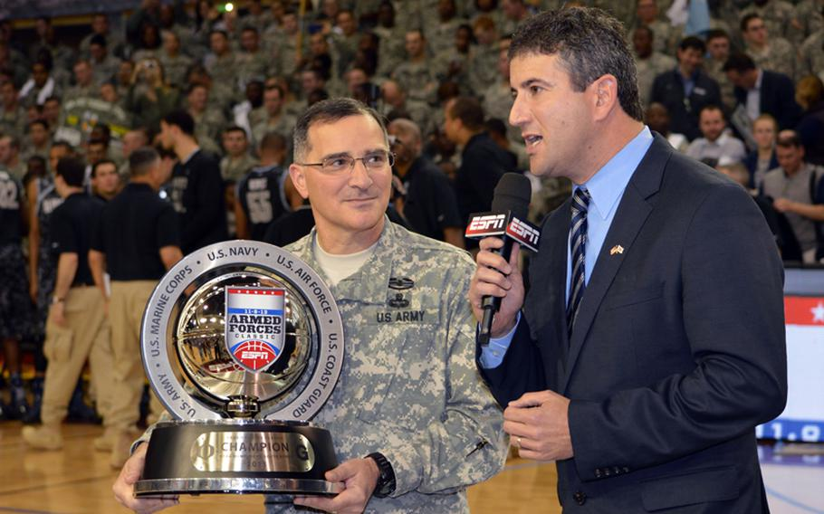 Gen. Curtis M. Scaparrotti, United Nations Command, Combined Forces Command and U.S. Forces Korea commander, presents the 2013 Armed Forces Classic basketball trophy to Oregon at Camp Humphreys, South Korea, on Saturday, Nov. 9, 2013. Oregon beat Georgetown 82-75.