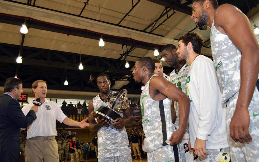Oregon is presented with the 2013 Armed Forces Classic basketball trophy at Camp Humphreys, South Korea, on Saturday, Nov. 9, 2013. The Ducks beat the Georgetown Hoyas 82-75 in the NCAA season-opener.
