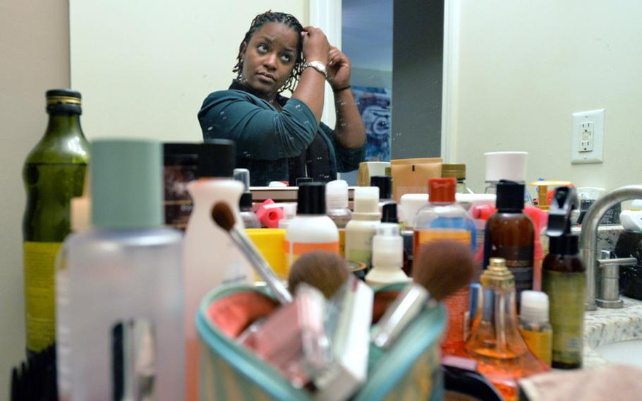 Jasmine Jacobs uses many products to do her daily hair treatment at her home in Atlanta on Tuesday, April 2, 2014. Jacobs, 6 years into what she thought was a promising and long military career, objects to a new policy that places heavy restrictions on how women can and cannot wear their hair in the military.