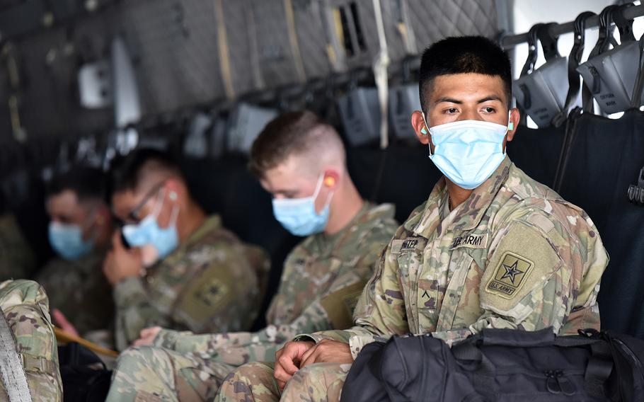 A soldier looks out of the loading ramp of a C-27 aircraft while he and his fellow soldiers wear face masks and maintain social distance.