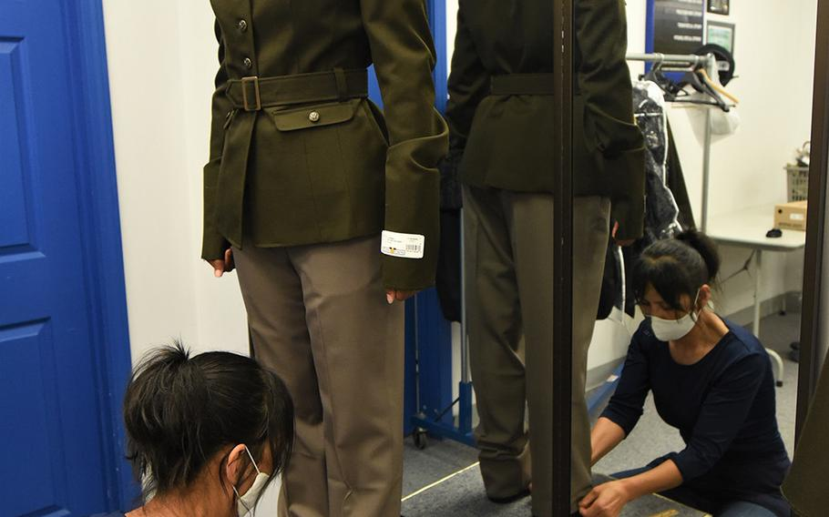 A female soldier attending the Army Recruiter Course at Fort Knox, Ky., has her pants hem measured by a seamstress after receiving the Army Green Service Uniform, July 8, 2020.