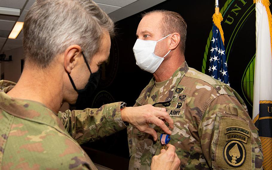 Gen. Richard D. Clarke, commander, U.S. Special Operations Command, presents Lt. Col. Larry Wyatt, USSOCOM clinic director, with a Soldier's Medal at MacDill Air Force Base, Fla., Dec. 22, 2020. Wyatt was awarded the medal for delivering lifesaving care to two people after a motorcycle collided with bicyclists April 7, 2019, despite being injured himself.