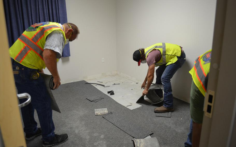 Civilian employees of the 502nd Civil Engineer Group remove carpet Thursday from a dorm room where mold was found in building 1215 at Lackland Air Force Base in Texas. Nearly 30 rooms in the building were found to have mold.