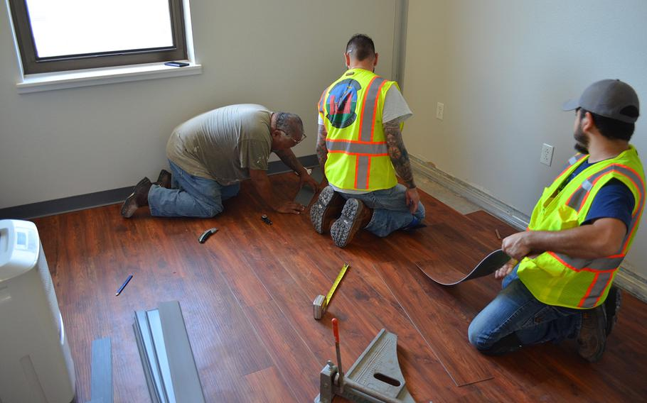 Civilian employees of the 502nd Civil Engineer Group lay new flooring Thursday in a dorm room where mold was found in building 1215 at Lackland Air Force Base in Texas. About one in six rooms at Joint Base San Antonio was found to have mold.