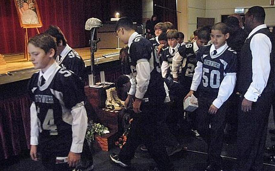 Members of Grafenwoehr's youth football team pay respects to Staff Sgt. Daniel A. Quintana, an assistant coach and a soldier with the 172nd Separate Infantry Brigade who was killed in Afghanistan on Sept. 10.