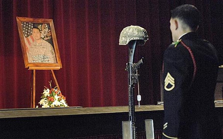 A soldier pays his respects at Wednesday's memorial service for Staff Sgt. Daniel A. Quintana in Grafenwoehr, Germany. A soldier with the 172nd Separate Infantry Brigade, Quintana was killed in Afghanistan on Sept. 10.