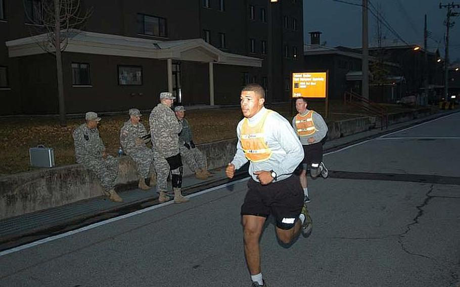 Spc. Devin Sanders, back, takes part in the two-mile run portion of his unit physical fitness test Nov. 7, 2012, at Camp Red Cloud in South Korea in advance of his planned attendance at Warrior Leader Course. Sgt. Adan Altagracia, front, sets the pace for Sanders in trying to help him maximize his fitness score. The Army this month reinstituted physical fitness standards required for participation in professional military education courses.