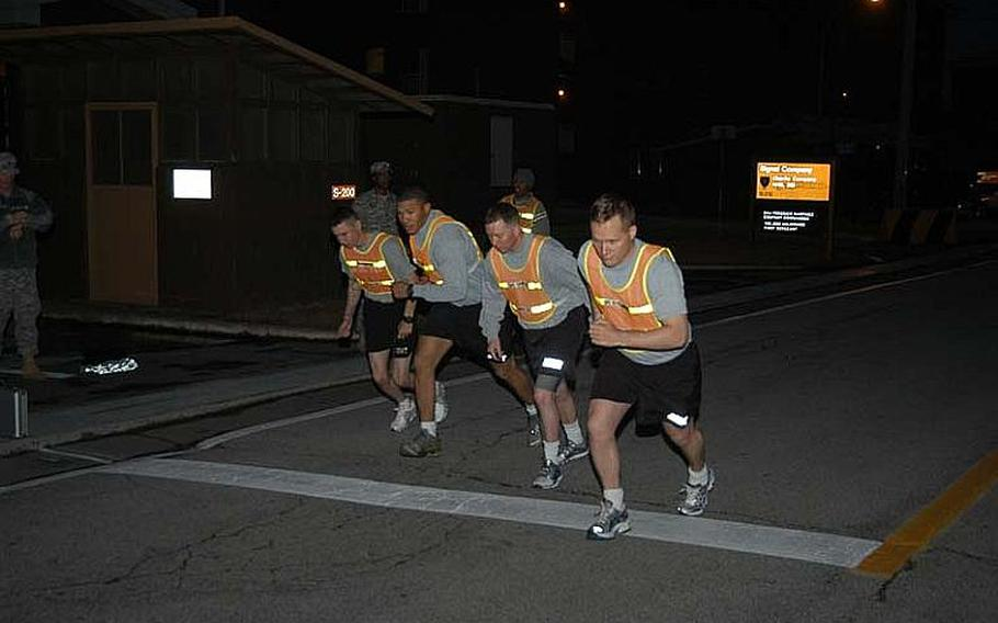 Soldiers start the two-mile run portion of their unit physical fitness test before sunrise on Nov. 7, 2012, at Camp Red Cloud in South Korea. The Army this month reinstituted physical fitness standards required for participation in professional military education courses.