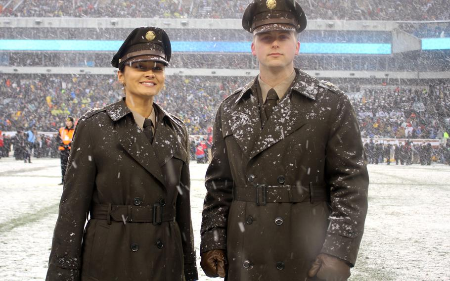 """Soldiers modeling the proposed """"pinks and greens"""" daily service uniform pose in their overcoats at Lincoln Financial Field in Philadelphia during the Army-Navy Game in December 2017."""