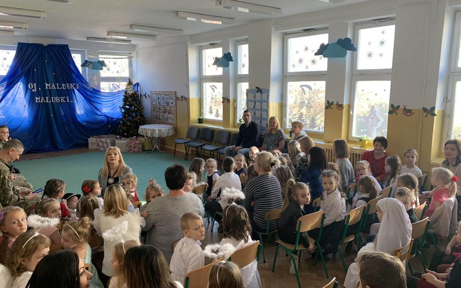 U.S. and Romanian soldiers, along with other guests, await a singing competition at the Miejskie Przedszkole school in Elk, Poland, Feb. 5, 2020.
