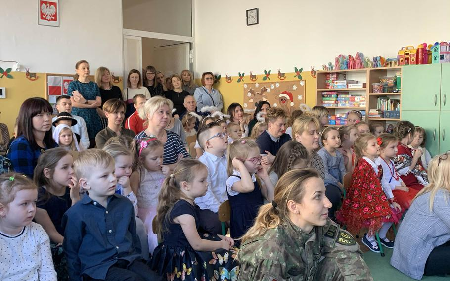 A Romanian soldier, right, and guests watch a singing competition at the Miejskie Przedszkole school in Elk, Poland, Feb. 5, 2020.