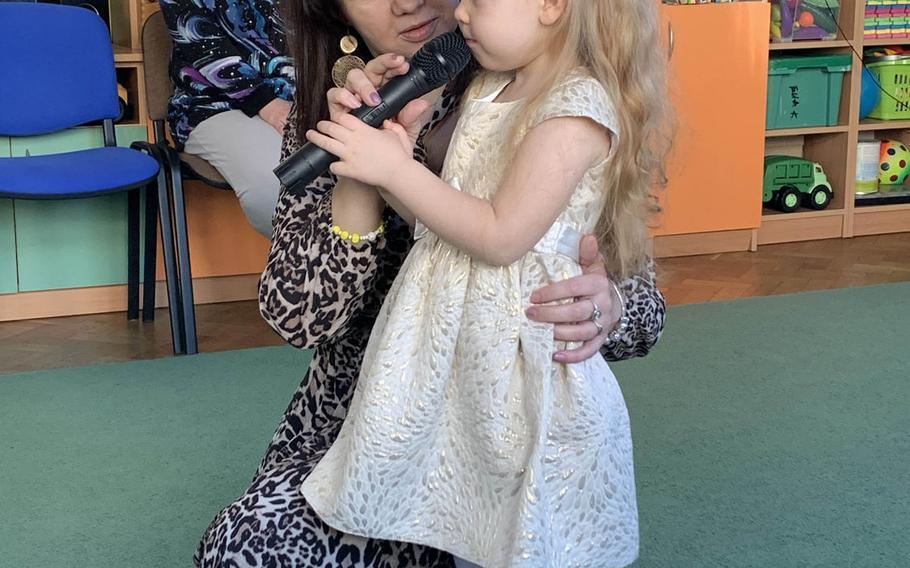 Edyta Dabrowska, a teacher, helps Kindze Rydzewskiej, center, as she sings at the Miejskie Przedskole school in Elk, Poland, Feb. 5, 2020.
