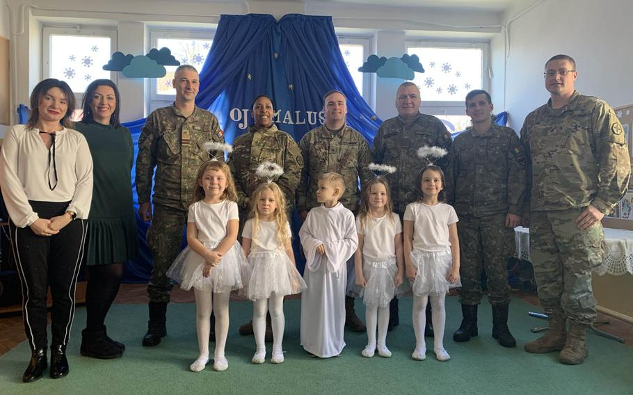 U.S. and Romanian soldiers pose with students and others following a children's concert at the Miejskie Przedszkole school in Elk, Poland, Feb. 5, 2020.