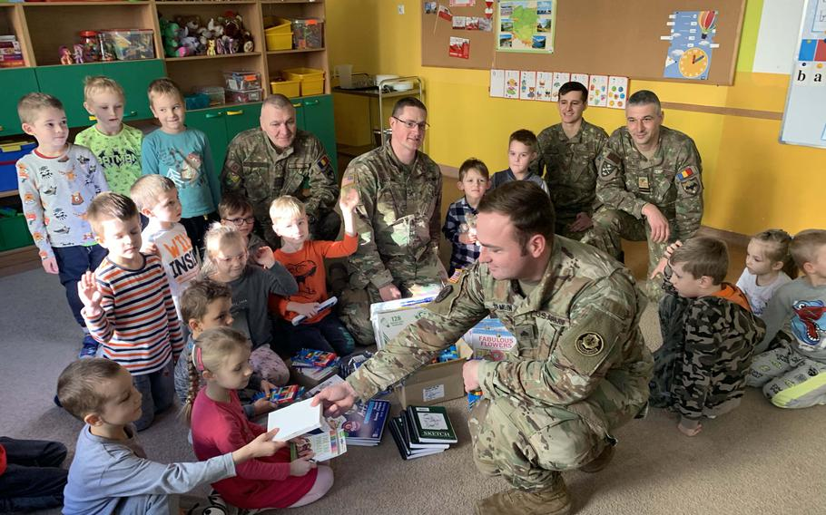 Army Sgt. Timothy Hamlin, front, hands out school supplies to children at the Miejskie Przedszkole school in Elk, Poland, Feb. 5, 2020.