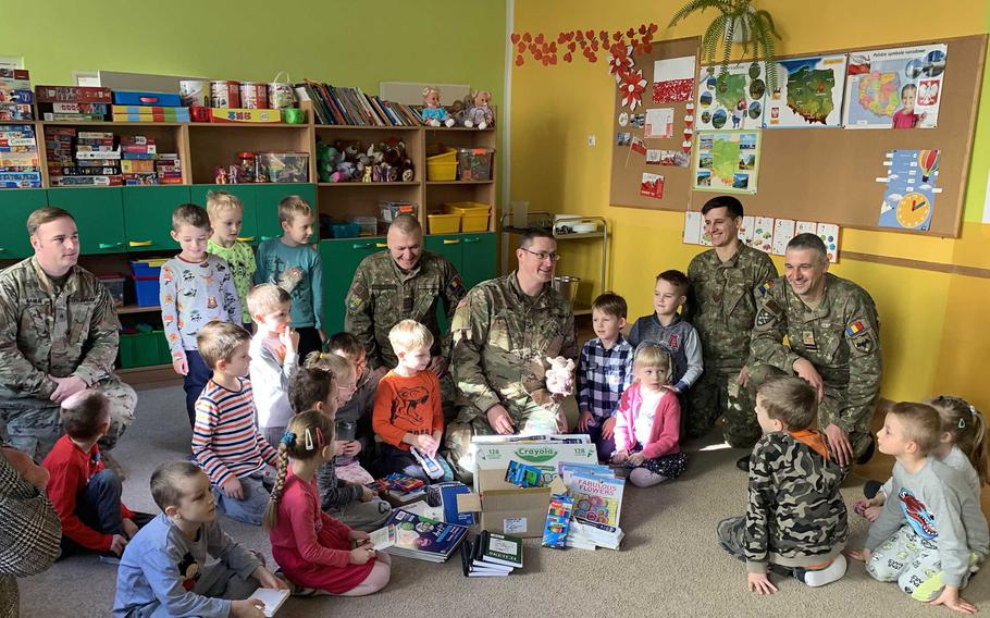 U.S. and Romanian soldiers talk with children after giving out school supplies at the Miejskie Przedszkole school in Elk, Poland, Feb. 5, 2020.