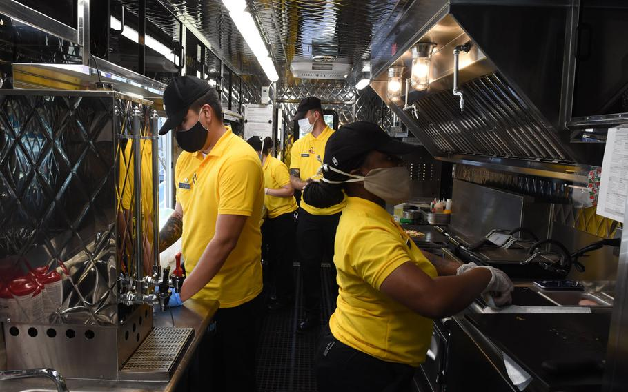 Army culinary specialists with the 55th Quartermaster Company, 16th Special Troops Battalion, 16th Sustainment Brigade, work in the narrow kitchen of the Culinary Outpost, the Army's first food truck in Europe, on Wednesday, June 3, 2020.
