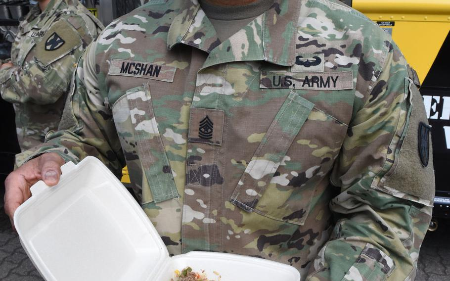 Army Sgt. Maj. Larry McShan holds up his order from the Culinary Outpost food truck on Wednesday, June 3, 2020, at Panzer Kaserne in Kaiserslautern, Germany. McShan ordered an Asian bowl with grilled teriyaki chicken and vegetables with white rice.