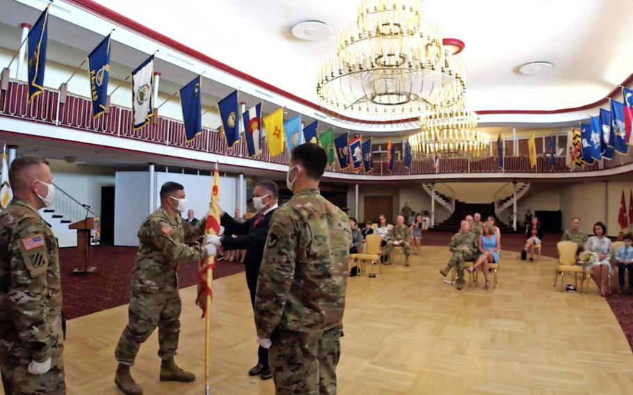 In this screenshot from the change of command ceremony in Kaiserslautern, Germany, July 22, 2020, outgoing U.S. Army Garrison Rheinland-Pfalz commander Col. Jason Edwards passes the unit's colors to Tommy Mize, director of Installation Management Command-Europe, as incoming commander Col. Vance J. Klosinski watches at right. At left is Command Sgt. Maj. Brett Waterhouse.