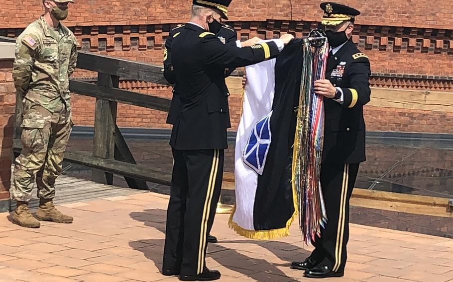 U.S. Army Chief of Staff Gen. James C. McConville and Lt. Gen. John Kolasheski, V Corps commanding general, officially unfurl the V Corps flag during a ceremony in Krakow, Poland, Aug. 4, 2020. The city of Poznan, Poland, will be the location of V Corps' forward headquarters in Europe, the Army announced Sept. 9, 2020.