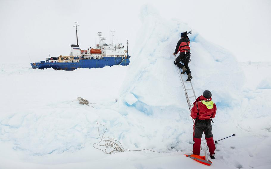 In this Tuesday, Dec. 31, 2013 image provided by Australasian Antarctic Expedition/Footloose Fotography, Ben Maddison and Ben Fisk from the Russian ship MV Akademik Shokalskiy work to place a wind indicator atop an ice feature near the trapped ship 1,500 nautical miles south of Hobart, Australia. Passengers on board a research ship that has been trapped in Antarctic ice for a week are expected to be rescued by helicopter, after three icebreakers failed to reach the paralyzed vessel, officials said Tuesday.