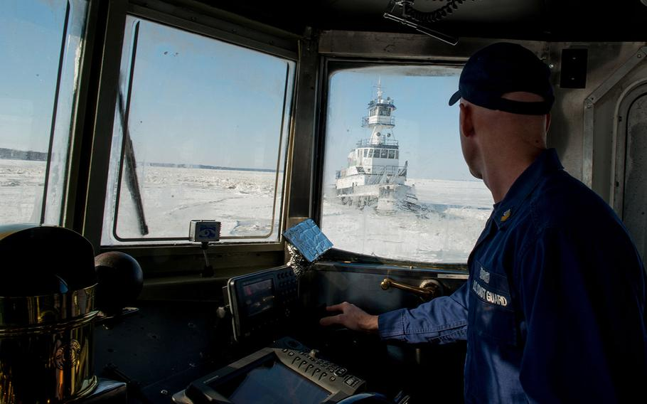 Petty Officer 1st Class Ben Heinze navigates the Coast Guard Cutter Cleat, a 65-foot ice breaking-tug, to help free a local tugboat stuck in the upper Chesapeake Bay ice Friday, Feb. 20, 2015.