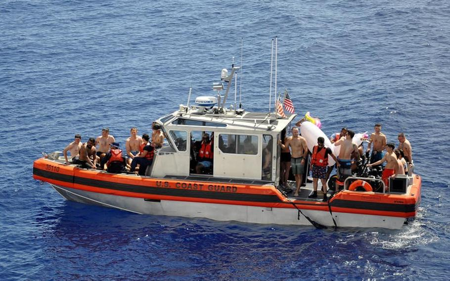 U.S. Coast Guard members board a boat to escape a shark seen during a U.S. Coast Guard Cutter Kimball swim call, somewhere in Oceania on Aug. 21, 2020.
