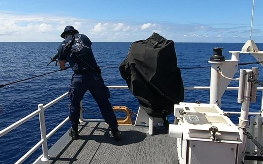A U.S. Coast Guard members fires into the water during a swim call, to scare away a shark, somewhere in Oceania on Aug. 21, 2020. The USCG says they were well aimed shots and they didn't hurt any of the nearby swimmers, including the shark.