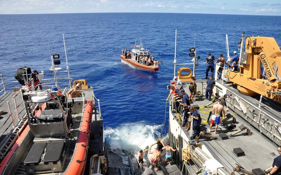 U.S. Coast Guard members board a boat to escape a shark seen during a U.S. Coast Guard Cutter Kimball swim call, somewhere in Oceania on Aug. 21, 2020