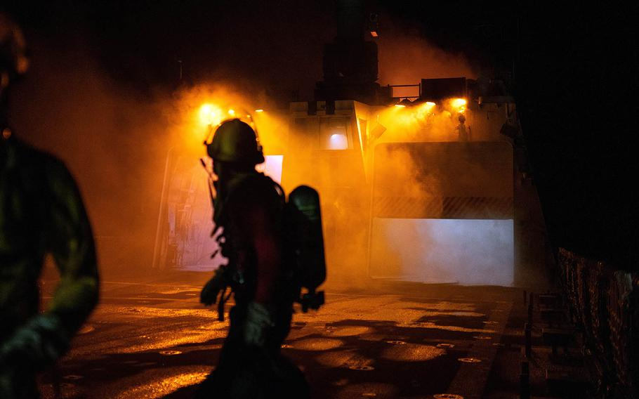An investigator aboard the Coast Guard cutter Waesche looks back toward the superstructure after the vessel caught fire in the Pacific Ocean, Sept. 19, 2020.