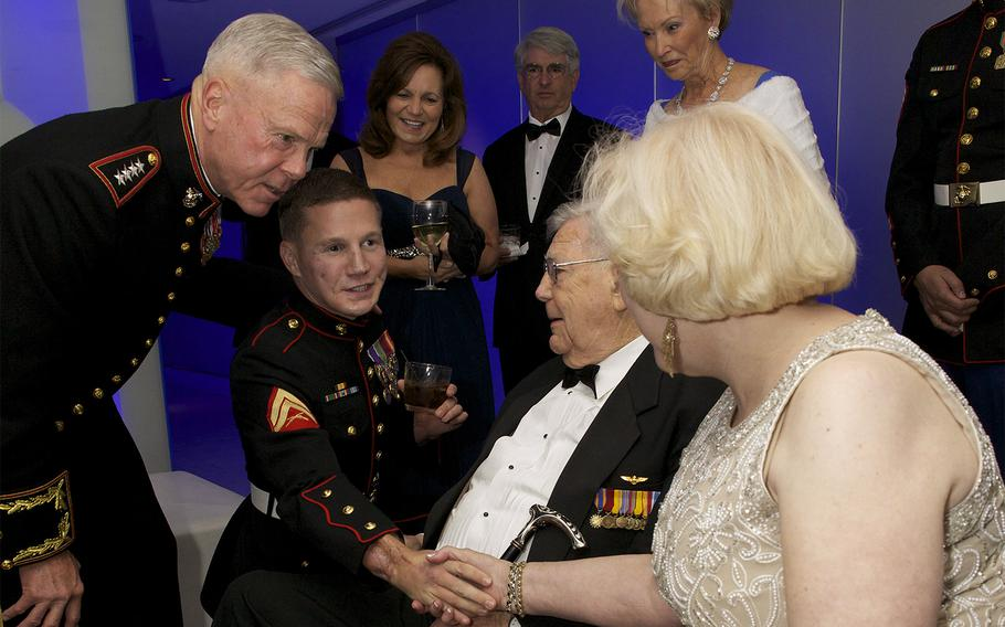 Marine Cpl. William Kyle Carpenter kneels beside Gen. James F. Amos, the 35th Commandant of the Marine Corps, while being introduced to guests at the Gaylord National Resort and Convention Center, at the National Harbor in Maryland on Nov. 9, 2013.