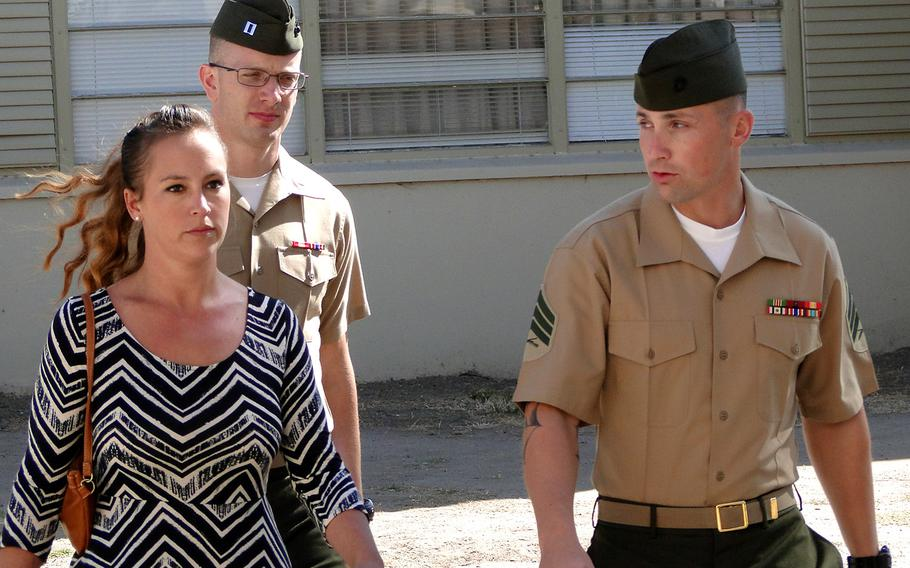 """Sgt. Lawrence G. Hutchins III and his wife, Reyna, walk into a pre-trial hearing at Camp Pendleton in October 2014. A Marine general said Thursday, March 6, 2015, that his decision to order a retrial for Hutchins in the killing of an Iraqi civilian was not affected by Navy Secretary Ray Mabus' statement that the victim """"was murdered."""""""