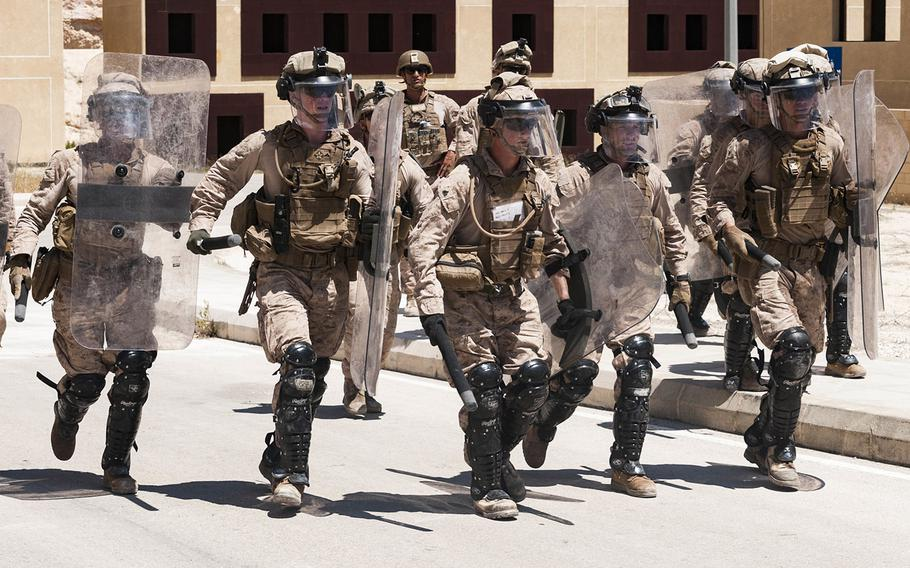 A team of U.S. Marines carrying riot shields rush to secure a defensive line during embassy reinforcement training near Amman, Jordan, April 23, 2018, as part of Exercise Eager Lion 18.