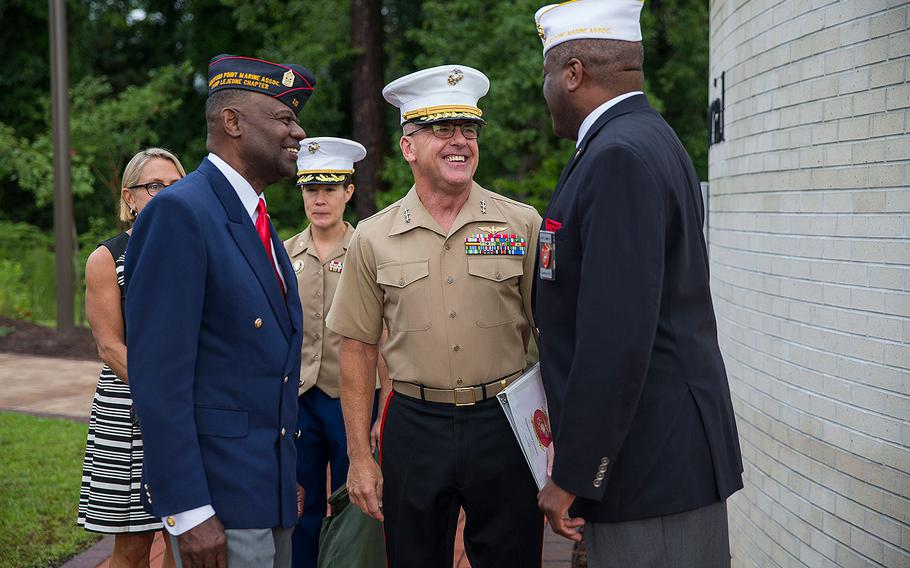 Lt. Gen. Robert F. Hedelund, commanding general, II Marine Expeditionary Force, center, is greeted by Forest Spencer, right, national president, Montford Point Marine Association, during the Montford Point Marine Memorial gifting ceremony at the Montford Point Marine Memorial in Jacksonville, N.C., July 25, 2018.