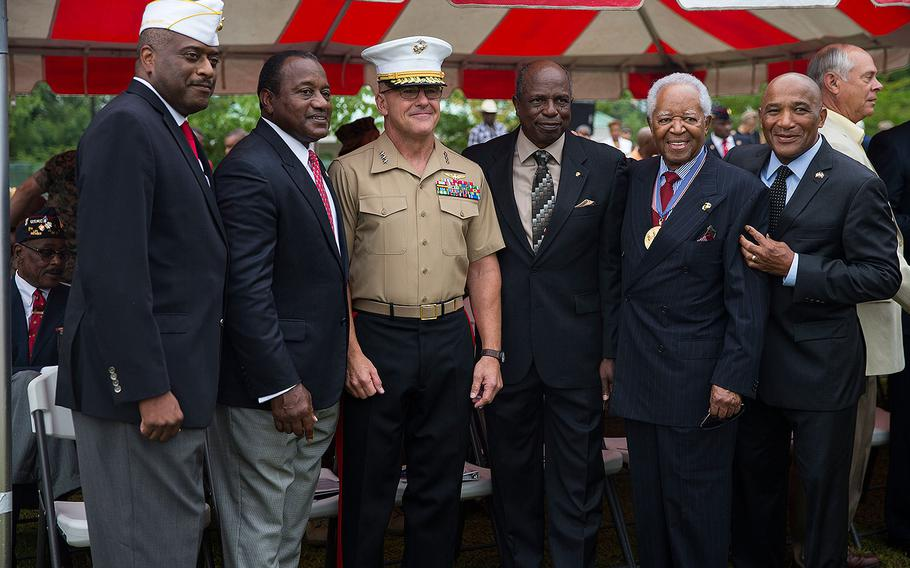 Guests pose with Lt. Gen. Robert F. Hedelund, commanding general, II Marine Expeditionary Force, during the Montford Point Marine Memorial gifting ceremony at the Montford Point Marine Memorial in Jacksonville, N.C., July 25, 2018.