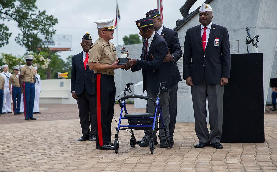 Retired U.S. Marine Sgt. John Spencer, Montford Point Marine, presents a gift to Lt. Gen. Robert F. Hedelund, commanding general, II Marine Expeditionary Force, during the Montford Point Marine Memorial gifting ceremony at the Montford Point Marine Memorial in Jacksonville, N.C., July 25, 2018.