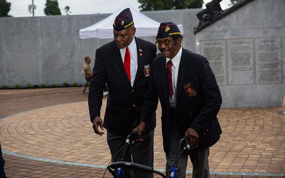 Retired U.S. Marine Col. Grover C. Lewis III, left, escorts, retired U.S. Marine Sgt. John Spencer, right, to his seat during the Montford Point Marine Memorial gifting ceremony at the Montford Point Marine Memorial in Jacksonville, N.C., July 25, 2018.