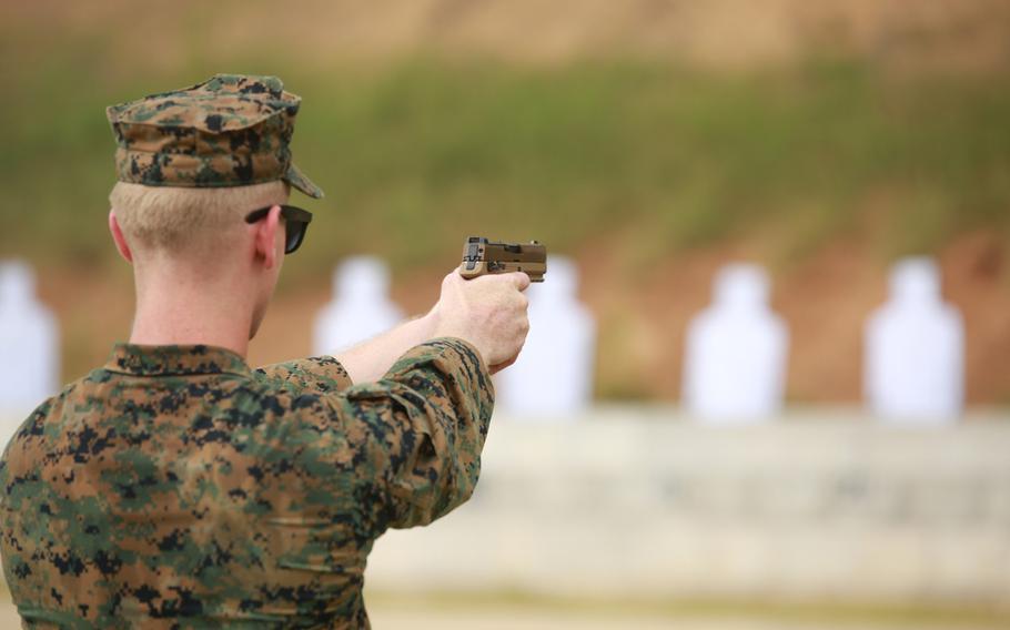 A Marine instructor shoots the M18 handgun at a firing range during training June 25, 2020, at Marine Corps Base Quantico, Va.